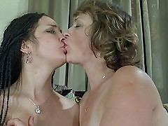 Two aroused lesbians licking muffs in 69 on couch