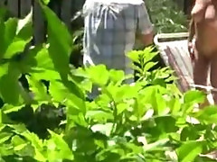 Pervert peeping on busty naked chick on a photoshoot outdoor
